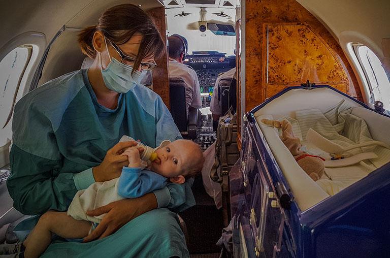 Eine Intensivkrankenschwester sitzt im Ambulanzjet und versorgt einen neugeborenen Patienten mit Milch.