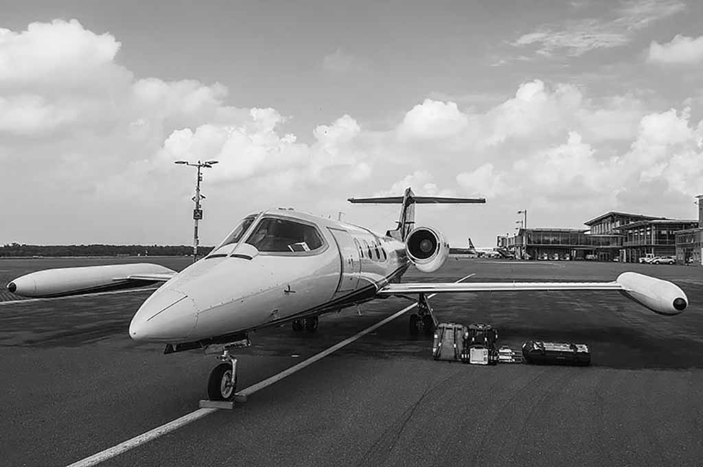 Ein Ambulanzjet steht auf dem Rollfeld eines Flughafens. Unter der linken Tragfläche stehen drei Gepäckstücke eines Patienten.