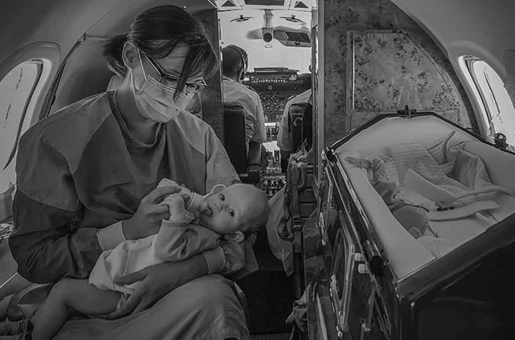 Eine Kinderintensivschwester mit Mundschutz hat ein kleines Baby auf dem Arm und füttert es mit einer Flasche Milch.