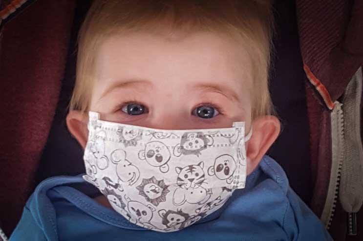 Kleinkind mit Mundschutz unterwegs mit unserer Flugambulanz