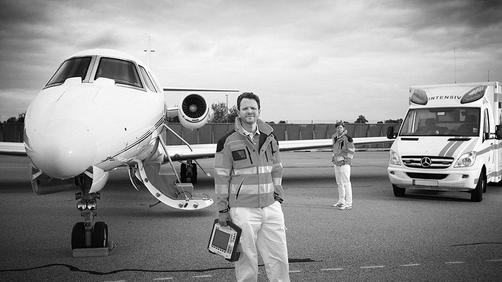Dr. med. Matthias Hübner steht auf einem Vorfeld vor einem Ambulanzjet. Links davon steht ein Intensivtransportwagen.