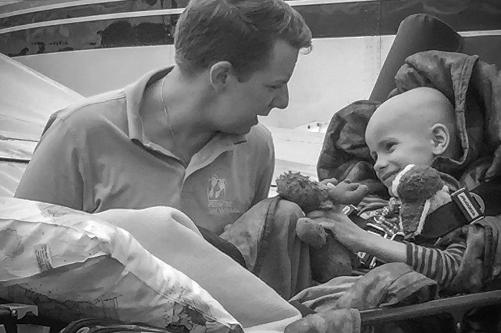 Zwei Fachärzte betreten, als medizinische Flugbegleiter, mit einer kleinen Patientin auf dem Arm ein Flugzeug.
